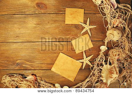 Card blanks with sea stars and shells on wooden background
