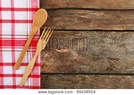 Checkered napkin with fork and spoon on wooden table background