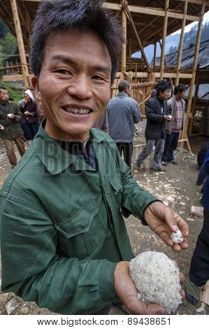 Chinese Peasant Holding A Portion Of Cooked Rice