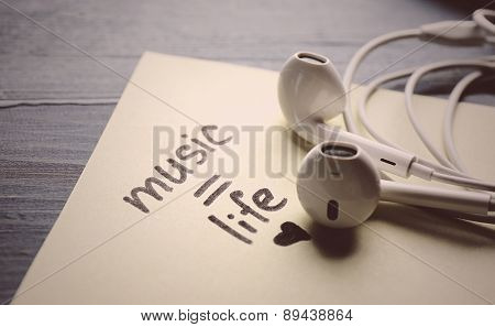 Earphones with text Music - life on sticker on wooden table, closeup