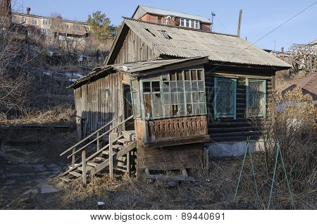 Old rickety launched wooden house with ladder and porch