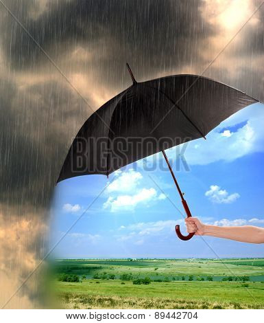 Black umbrella in hand protecting good weather from dark clouds of rain