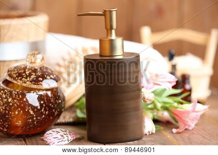 Beautiful spa composition with cosmetic bottle and flower on table close up
