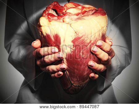 Woman holding raw animal heart close up