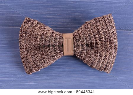 Male bow tie on color wooden table background