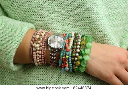 Stylish bracelets and clock on female hand close-up