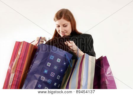 Young attractive woman with shopping bags on a white background