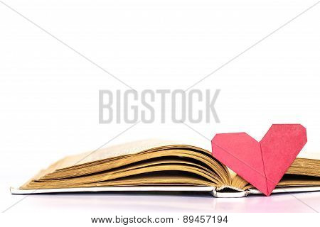 Open book with origami heart isolated on white background