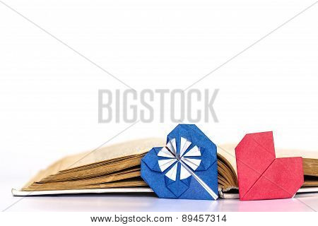 Open favorite literature with two origami hearts - red and blue.