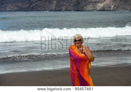 Aged Woman On Surf Waves And Cliff Background.