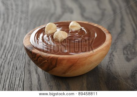 chocolate hazelnut creamin wood bowl, on old table
