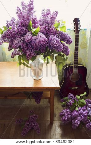 Romantic Interior Design With Lilac Flowers And Red Guitar