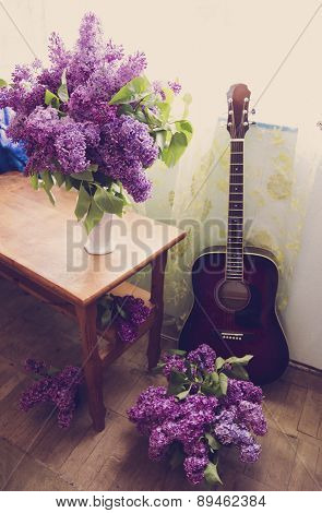 Romantic Interior Design With Lilac Flowers And Red Guitar In Warm Tones
