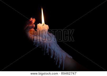 Open Hand Holding Candle Stick With Wax Flowing Down The Arm