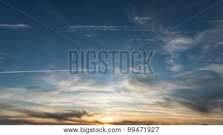 skyscape at sunset with plane  trails