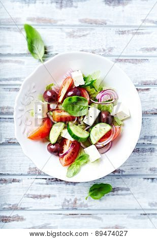 Bowl of colorful summer salad with feta and olives