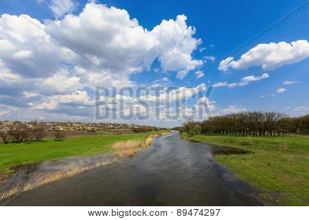 Spring landscape on river under nice clouds in sky