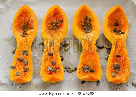 Four Butternut Squash Pieces With Pumpkin Seeds On White Paper