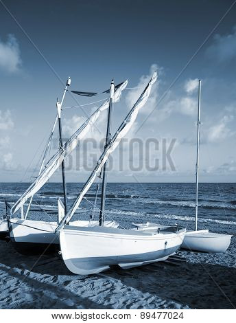 Small White Sailing Boats Lay On The Sandy Beach