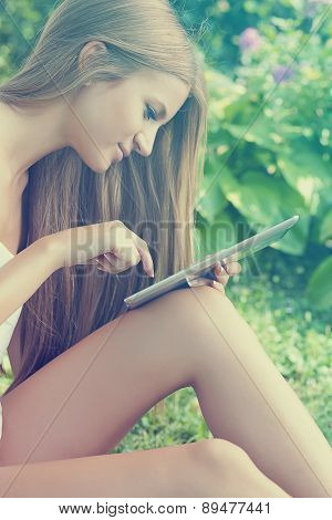 Beautiful Woman Using Tablet Computer In Garden, Park