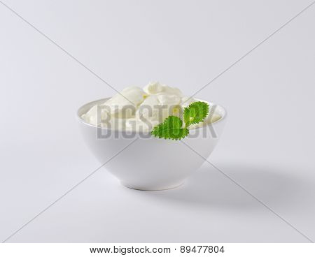 portion of fresh white joghurt in the bowl, decorated with piece of mint