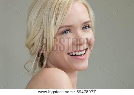 Beauty portrait of happy young woman isolated on grey background