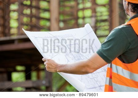 Midsection of male architect holding blueprint at construction site