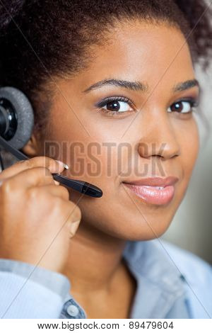 Portrait of young female customer service representative wearing headset in office