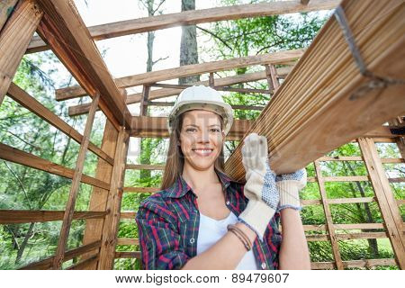 Portrait of happy female worker carrying wooden planks at construction site