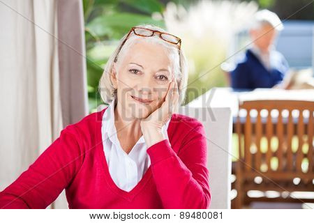 Portrait of beautiful senior woman sitting at nursing home with grandson in background