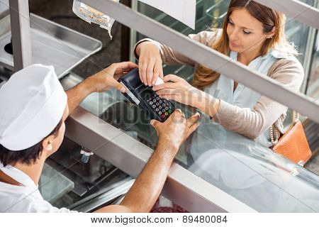 High angle view of female customer paying through smartphone at butcher's shop