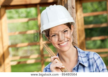 Portrait of beautiful architect holding measuring tape at construction site