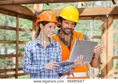 Male and female architects working on laptop together at construction site