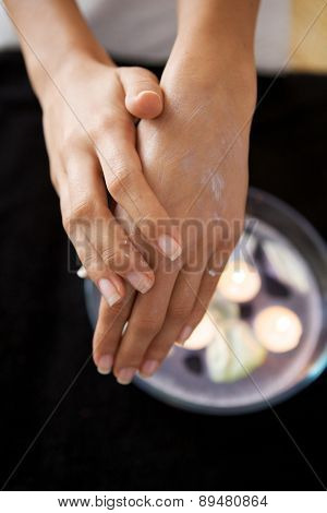 Close-up of woman rubbing lotion on hands