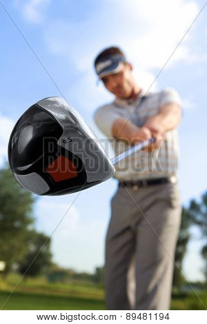 Young man playing golf, low angle view
