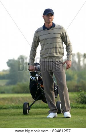 Young man carrying trolley with golf bag