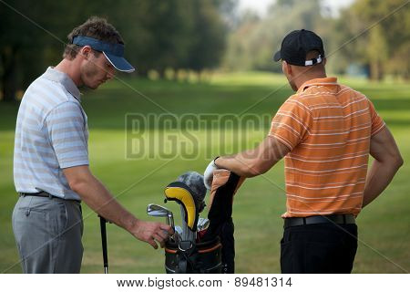 Young men standing in golf course by golf bag full of sticks