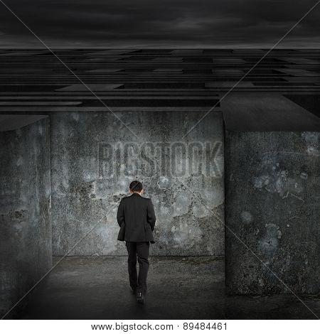 Businessman Walking Enter Dark Huge Maze With Cloudy Sky
