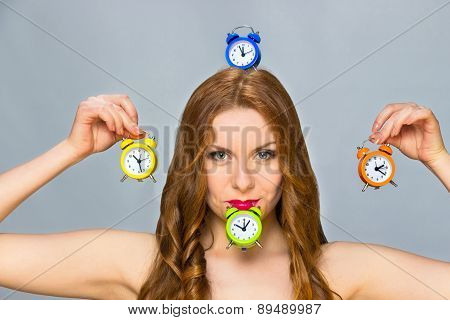Woman With Alarm Clocks On Grey Background