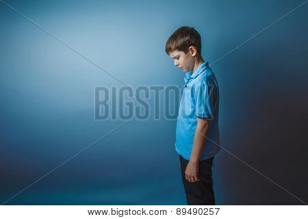 teenager boy Brown European appearance in a blue shirt stands si