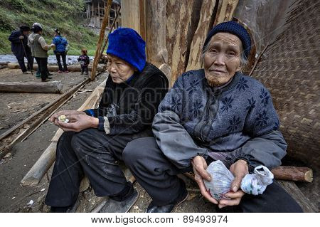 Two Older Farmer Asians, Rural Women, Sitting Near Peasant House.