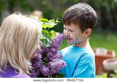 Little Boy Smell Lilac With Mother