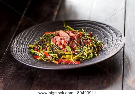 Authentic Salad With Bacon Fresh Red Pepper, Sprouts, Sesame And Olive Oil On A Black Plate. Morning