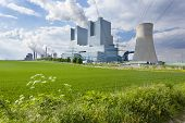 picture of fire-station  - A shiny new lignite power station behind a field with some flowers in the foreground and another power station in the background - JPG