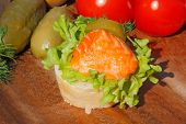 foto of baguette  - Slice of baguette with smoked salmon filet garnished with lettuce onion tomato and pickles on a wooden board - JPG