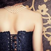 stock photo of corset  - woman wearing black corset and pearls against retro background - JPG