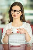 stock photo of pullovers  - Young beautiful girl in glasses and white pullover sitting in urban cafe with a cup of coffee - JPG