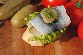 pic of baguette  - Baguette slice with sour herring pickled herring garnished with lettuce gerkin tomatoes and onion on a wooden board - JPG