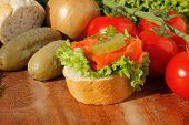 foto of baguette  - Slice of baguette with pollock fillet garnished with lettuce onion tomato and pickles on a wooden board - JPG