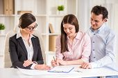 picture of contract  - Young couple signing financial contract with female realtor - JPG